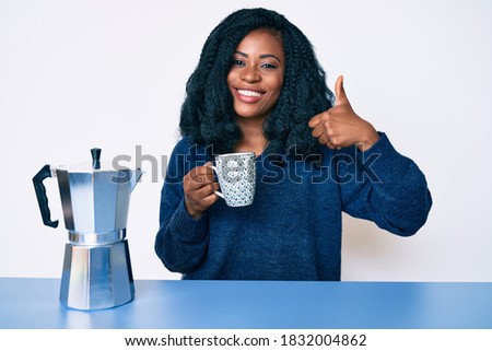Beautiful african woman drinking a coffee from italian coffee maker smiling happy and positive, thumb up doing excellent and approval sign