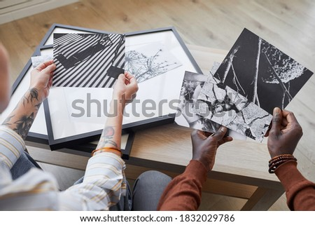 High angle close up of two modern young people discussing black and white pictures while choosing artwork for interior decor, copy space