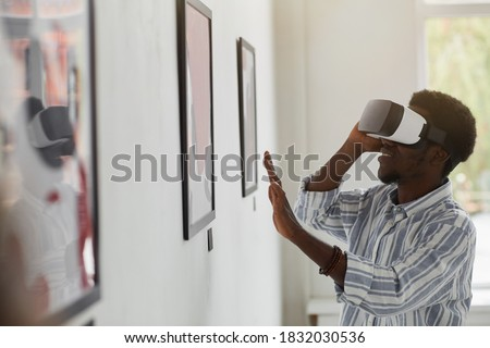 Side view portrait of smiling African-American man wearing VR gear while enjoying immersive experience at modern art gallery exhibition, copy space Royalty-Free Stock Photo #1832030536