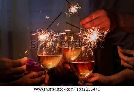 glasses with sparkling wine and sparkler is held by a company of people Royalty-Free Stock Photo #1832035471