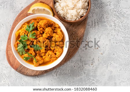 Cauliflower stew with curry, cumin, turmeric and other spices in a white bowl on a gray concrete background top view. Free space for text. Curry roasted cauliflower. Copy space. #1832088460