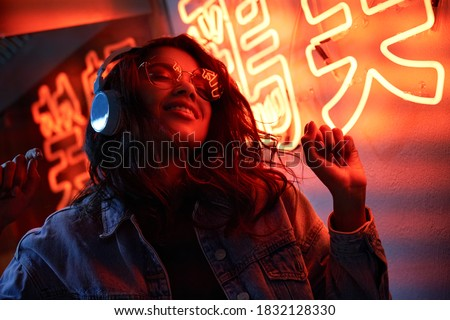 Happy cool fashion funky African young black hipster lady wears trendy glasses headphones listening dance pop dj music standing in neon night club light at style party. Translation: Chicken laugh Royalty-Free Stock Photo #1832128330
