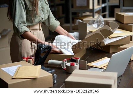 Closeup view of female online store small business owner seller entrepreneur packing package post shipping box preparing delivery parcel on table. Ecommerce dropshipping shipment service concept. Royalty-Free Stock Photo #1832128345