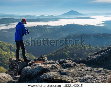 Nature photographer is checking the camera screen to see if his shot was a success. Tourist takes photos with smart phone on peak of hilly landscape.