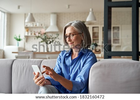 Relaxed mature old 60s woman, older middle aged female customer holding smartphone using mobile app, texting message, search ecommerce offers on cell phone technology device sitting on couch at home. Royalty-Free Stock Photo #1832160472