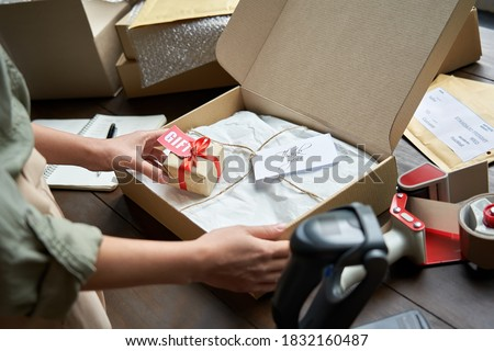 Female online store small business owner seller holding gift packing package post shipping box preparing delivery parcel on table. Ecommerce dropshipping holiday presents sale concept. Closeup. Royalty-Free Stock Photo #1832160487