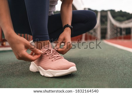 Close up of young woman getting ready for jogging outdoors while lacing her pink sneakers. Health and sport concept Royalty-Free Stock Photo #1832164540