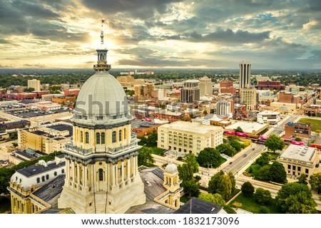 Aerial view of the Illinois State Capitol dome and Springfield skyline under a dramatic sunset. Springfield is the capital of the U.S. state of Illinois and the county seat of Sangamon County Royalty-Free Stock Photo #1832173096