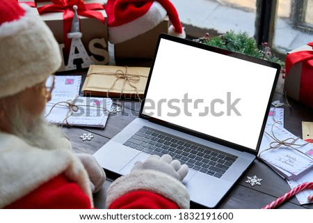 Over shoulder view of Santa Claus wearing costume using laptop computer with white blank empty mock up screen monitor sitting at workshop table on Merry Christmas eve. E commerce website ads concept #1832191600