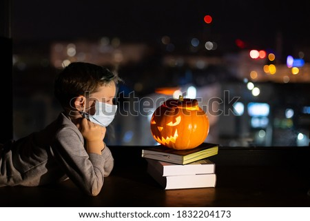 Sad boy celebrating halloween alone social distance. A child in a mask on the eve of all saints day. Kid in a protective medical mask. Covid-19 coronavirus pandemic 2020. treat or trick  no party