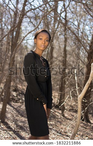 Photo of young African American woman standing in bare winter forest. Focus on the face, bokeh effect. Black shirt dress. Side on view.