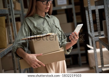 Female warehouse worker manager, small stock business owner holding phone and retail package parcel boxes checking commercial shipping delivery order on smartphone using mobile app technology. #1832219503