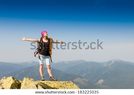 Hiker with backpack standing on top of a mountain and enjoying the view  #183225035