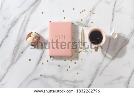 Pink coral colored diary for the year 2021, pen, coffee latte, macaron cookie and straw woven placemat on white marble background. New year planning concept. Minimalistic workstation. Copy space. #1832262796