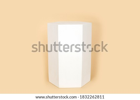 Hexaconal prism geometric figure in white color that casts shape on pastel beige color background. Three-dimensional shape with side in form of hexagon. geometric podium. Fashion magazine.