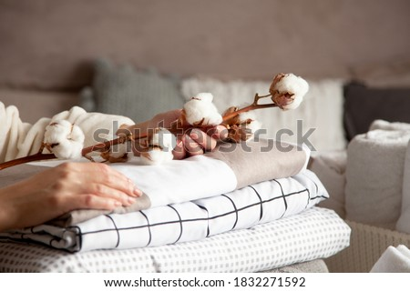 Well groomed woman hands holding the cotton branch with pile of neatly folded bed sheets, blankets and towels. Production of natural textile fibers. Manufacture. Organic product. #1832271592