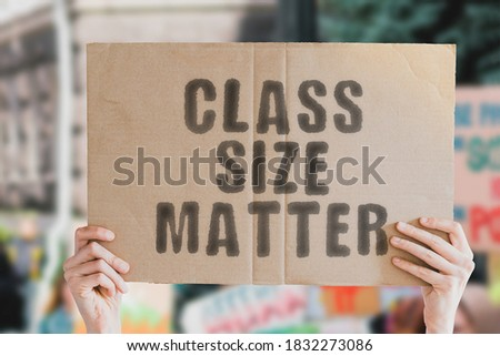 """The phrase """" Class size matter """" on a banner in men's hand with blurred background. Education. Occupation. Teaching. Teachers. School. College. Student. Studying. Profession. Salary Royalty-Free Stock Photo #1832273086"""