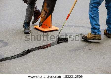 Road surface restoration work in the worker performs on road patcher work on the repair of cracks by filling and sealing with coated by bitumen emulsion asphalt surface. Royalty-Free Stock Photo #1832312509