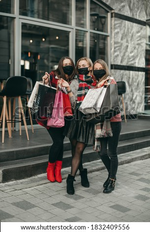 Three portrait of young happy women in medical masks and Christmas gifts walking in the city and shopping in quarantine. New year, packages, girlfriends, shop, coronavirus, pandemic Royalty-Free Stock Photo #1832409556