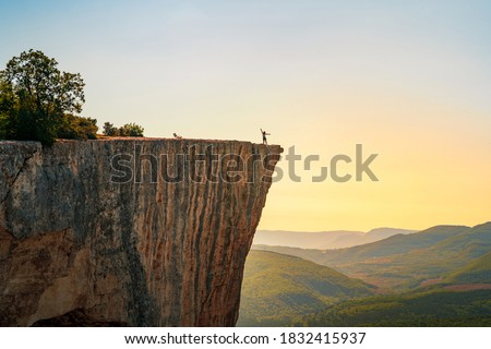 A small figure of a woman tourist with open arms, standing on the edge of a cliff in the summer mountains. The concept of a small man in the midst of a powerful nature. Royalty-Free Stock Photo #1832415937