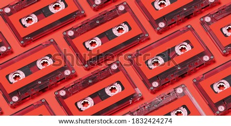 Minimal creative background for retro technology concept. Clear cassette tape with red label on red background. 3d rendering illustration. Clipping path of each element included.