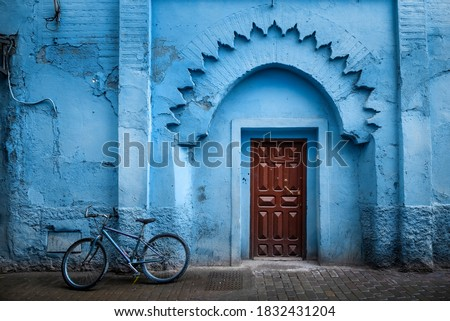 Traditional Moroccan ancient wooden entry door. In the old Medina in Chefchaouen, Morocco. Typical, old, blue intricately carved, studded, Moroccan riad door. Royalty-Free Stock Photo #1832431204