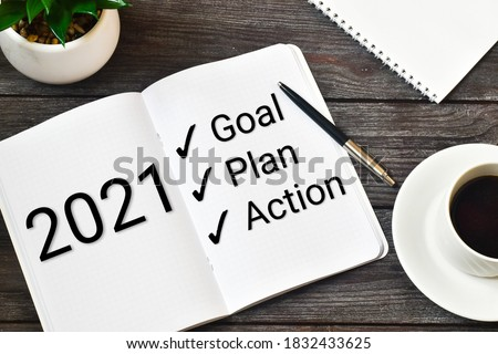 2021 New Year. Goal,plan, action text on notepad with office accessories on a wooden background. Business motivation, inspection concepts ideas. Royalty-Free Stock Photo #1832433625