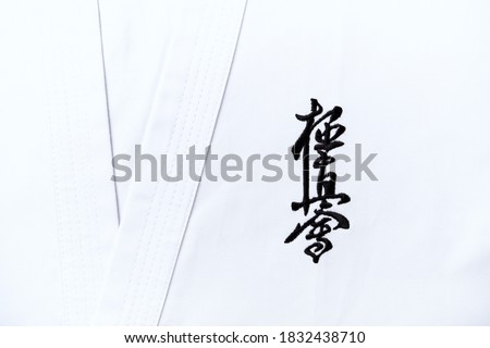 """Kyokushinkai karate symbol on cotton background. """"Kyokushin"""" is a style of stand-up, full contact karate and is Japanese for """"the ultimate truth"""". Royalty-Free Stock Photo #1832438710"""