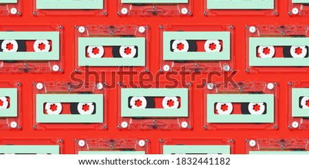 Minimal creative background for Christmas retro concept. Clear cassette tape with green label on red background. 3d rendering illustration. Clipping path of each element included.