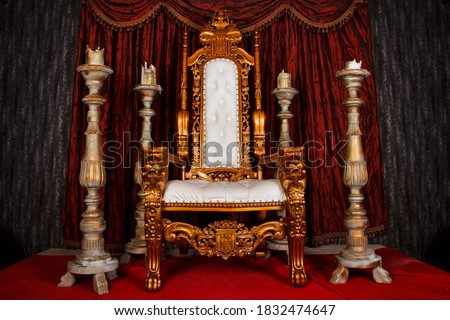 Old white and gold Royal chair with red curtains and candelabra in medieval vintage room. Throne for king in castle. Background in architecture or retro interior design. Copy space, text place