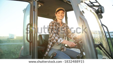 Portrait of beautiful Caucasian young woman in cap sitting in big tractor machine and smiling cheerfully to camera. Pretty happy female farmer worker in field at farm. Agricultural work. Royalty-Free Stock Photo #1832488915