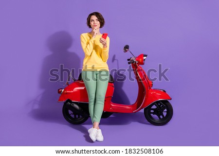 Full length body size view attractive cheery minded pensive girl sitting on bike using gadget creating blog post isolated over bright vivid shine vibrant lilac violet purple color background
