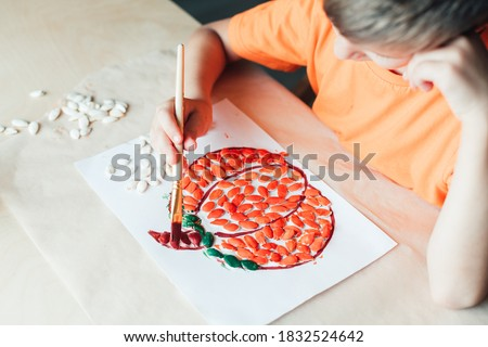 Boy making pumpkin from seeds on paper, Halloween DIY concept, child's hands make paper crafts Step by step instruction Step 3 Paint seeds with brown