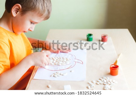 Happy boy making pumpkin picture from seeds on white paper, Halloween DIY concept. Step by step instruction. Step 2 Glue pumkin seeds onto the drawing