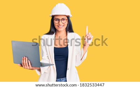Young beautiful latin girl wearing architect hardhat holding laptop surprised with an idea or question pointing finger with happy face, number one