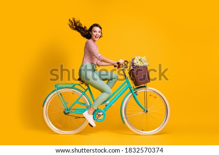 Full length body size side profile photo of cheerful girl riding blue bicycle with basket of flowers isolated on vibrant yellow color background Royalty-Free Stock Photo #1832570374