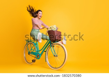 Full length body size photo of funny girl shouting riding bicycle keeping legs up isolated on vivid yellow color background Royalty-Free Stock Photo #1832570380