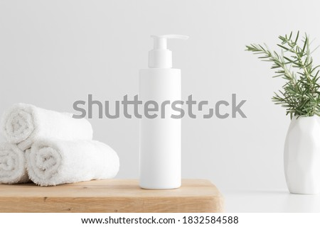 White cosmetic shampoo dispenser bottle mockup with towels and a rosemary  on a wooden table. Royalty-Free Stock Photo #1832584588