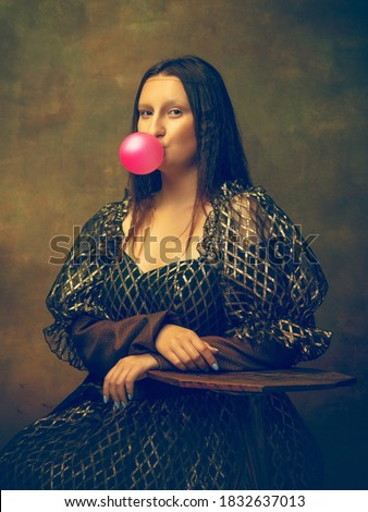 Bubble gum. Young woman as Mona Lisa, La Gioconda isolated on dark green background. Retro style, comparison of eras concept. Beautiful female model like classic historical character, old-fashioned. Royalty-Free Stock Photo #1832637013