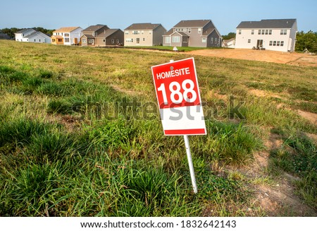 Empty, vacant home lots for sale sign with newly constructed homes in background in residential subdivision, grass plot, new construction, land parcel, homesite