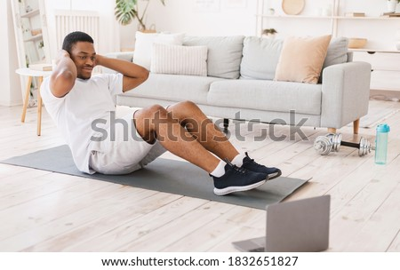 Home Training. Sporty African American Man Exercising Doing Sit-Ups Abs Exercise At Laptop Computer Indoors. Online Sport Workout, Morning Physical Training Exercises Concept Royalty-Free Stock Photo #1832651827