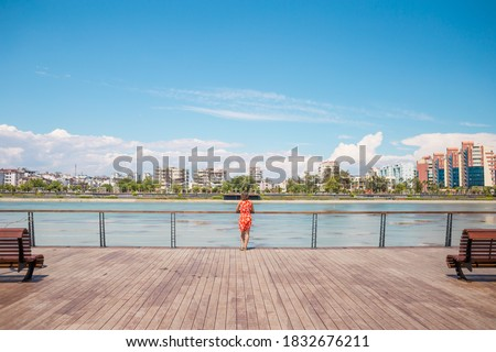 A girl in a dress walks on the promenade of Antalya, a woman stands on the banks of the river and looks at the water, the resort city of Turkey. Royalty-Free Stock Photo #1832676211