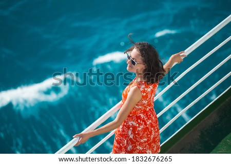 A woman is sailing on a cruise ship, a girl is standing near the fence on a ship and looking at the sea, traveling by ferry, a brunette in a summer dress admires the ocean. Royalty-Free Stock Photo #1832676265
