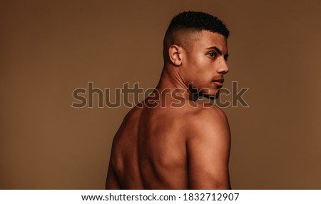 Portrait of shirtless muscular man looking away. Side view of african american man standing on brown background. Royalty-Free Stock Photo #1832712907