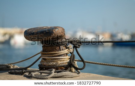 A rusty bollard with ropes. Fishing boats moor here in the port of Santa Pola in Spain. The background is out of focus with nice bokeh. Royalty-Free Stock Photo #1832727790