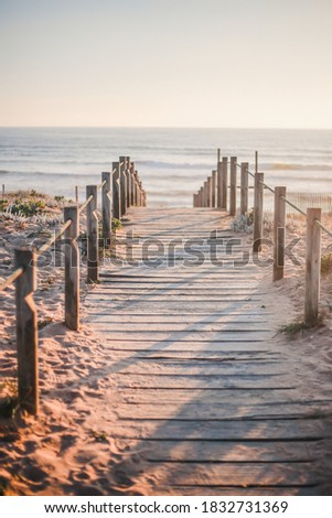 Wooden path on the beach during golden hour in Porto, Portugal Royalty-Free Stock Photo #1832731369