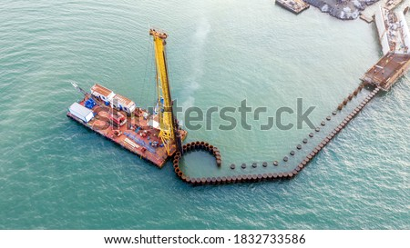 Aerial view of the piles of the under construction new pier and A pile driver. Pile driver is a device used to drive piles into soil to provide foundation support for buildings or other structures.  #1832733586