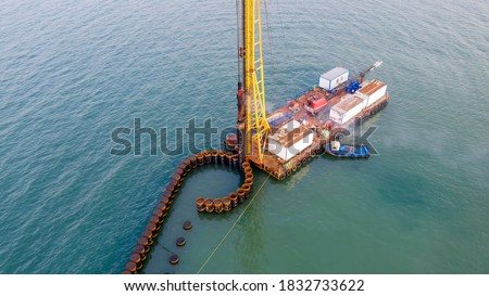 Aerial view of the piles of the under construction new pier and A pile driver. Pile driver is a device used to drive piles into soil to provide foundation support for buildings or other structures.  #1832733622