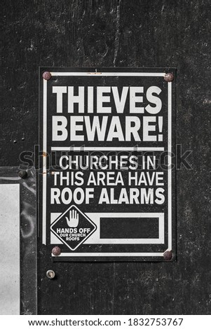 Warning sign on a dark wooden church door to ward off potential thieves.