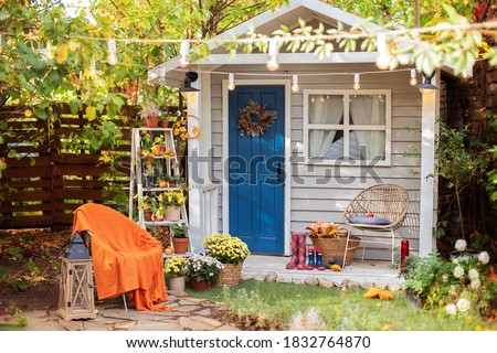 Cozy wooden house porch with chair, blanket, potted chrysanthemums and pumpkins. Decor outdoor of autumn yard. Facade House decorated for autumn holidays. Exterior autumn home. halloween. Autumn relax Royalty-Free Stock Photo #1832764870